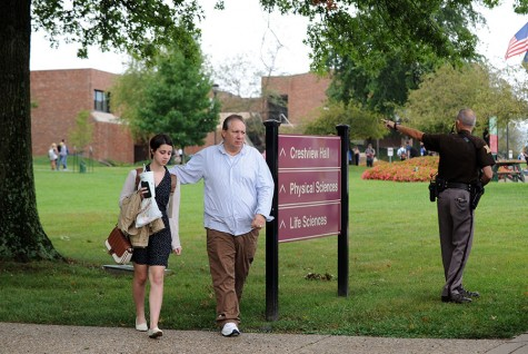 Greg Ezell, Jeffersonville, walks his daughter, Kymber, to their vehicle in the Indiana University Southeast parking lot following a lock-down stemming from reports of an armed gunman on campus. The false alarm was triggered after a student reported seeing what looked to be a gun handle sticking out of a camouflage backpack. Emergency responders arrived on campus around 1 p.m. where they identified the object as a large umbrella and the issue was then resolved.