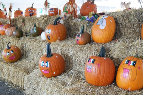 Huber's employees paint decorative faces on pumpkins to sell to the public.