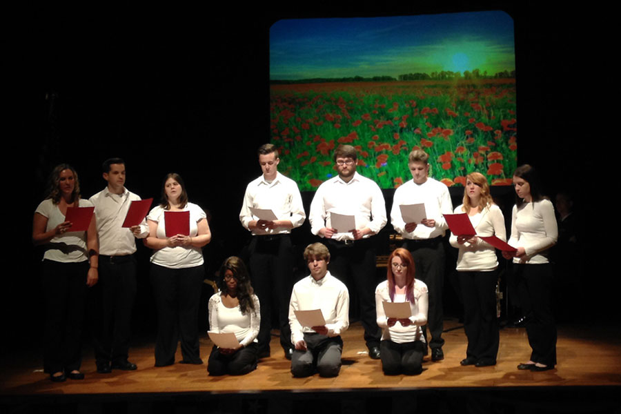 "A group of communications students does a public reading of ""In Flanders Fields"" by John McCrae for the program. The students are from an Oral Interpretation of Literature class taught by Diane Reid, senior lecturer of communications."