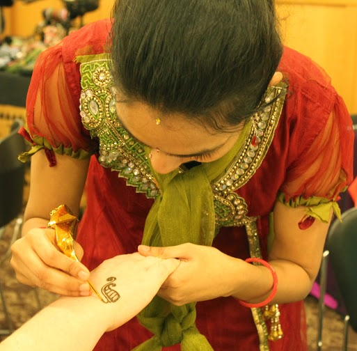 Ishwarya Iyer, adjunct professor of social informatics, tattoos henna at International Festival