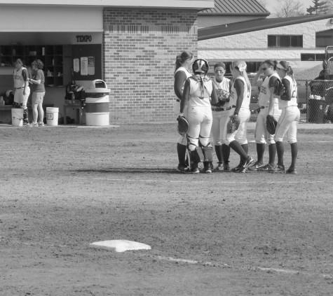 IU Southeast softball players talk on the field
