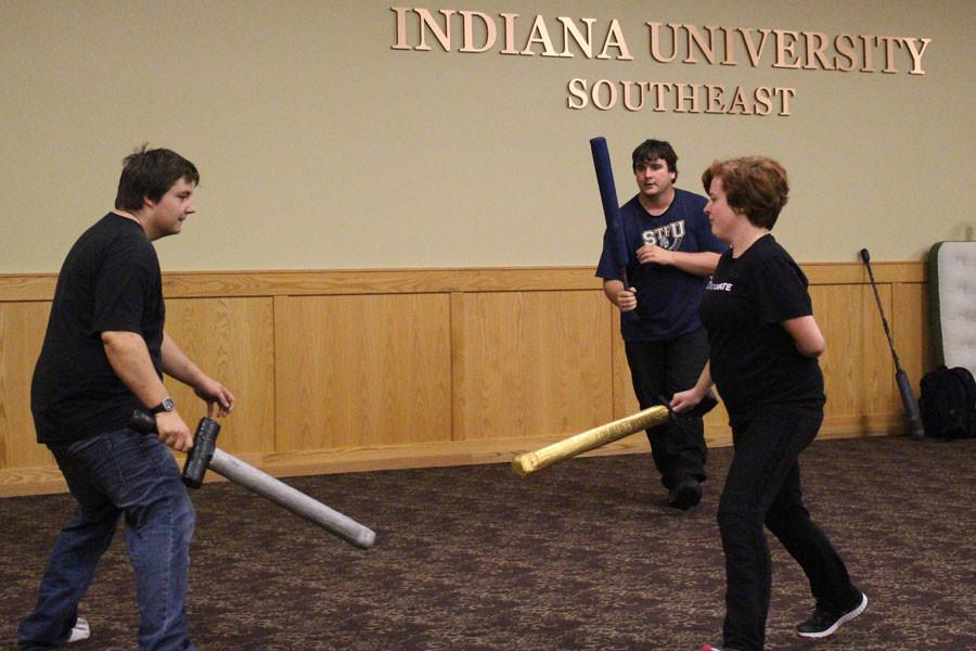 """Sophomore computer science Michael Hartsfield and sophomore Spanish Amanda Miles team up against sophomore computer science Logan Johnson in a sword fight. """"It gets the blood pumping. The fantasy element and violence is fun,"""" Johnson said."""