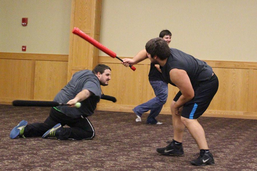 """Randall Moyes slides on his knees to attack general studies senior Daniel Wells. Wells participates in a variety of games offered by the society. """"It's fun exercise and a good chance to meet new people. You get to hit people too,"""" said Wells."""