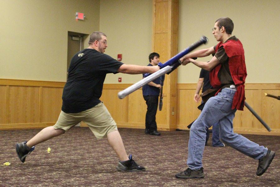 While practicing before the big encounter, Eric Razor lunges at fire mage Jacob Lutz trying to best him in combat. Razor has volunteered with the gamers' society for three years and prefers the card game nights but enjoys the controlled violence LARPing provides. Lutz has volunteered for two years and participates in all of the events.