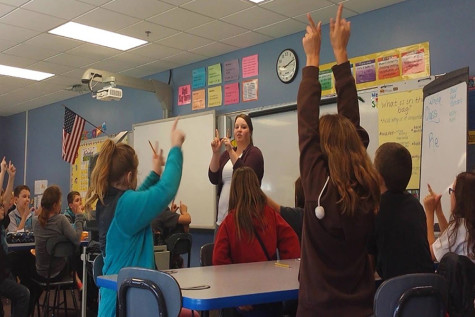 "(Standing) Shelby Royalty, education senior, teaches students a lesson about weathering in Susan Mosley's fourth-grade classroom at Corydon Intermediate School. ""We were making a W with our hands and then breaking it apart to show that weathering is the breaking of rocks,"" Royalty said."