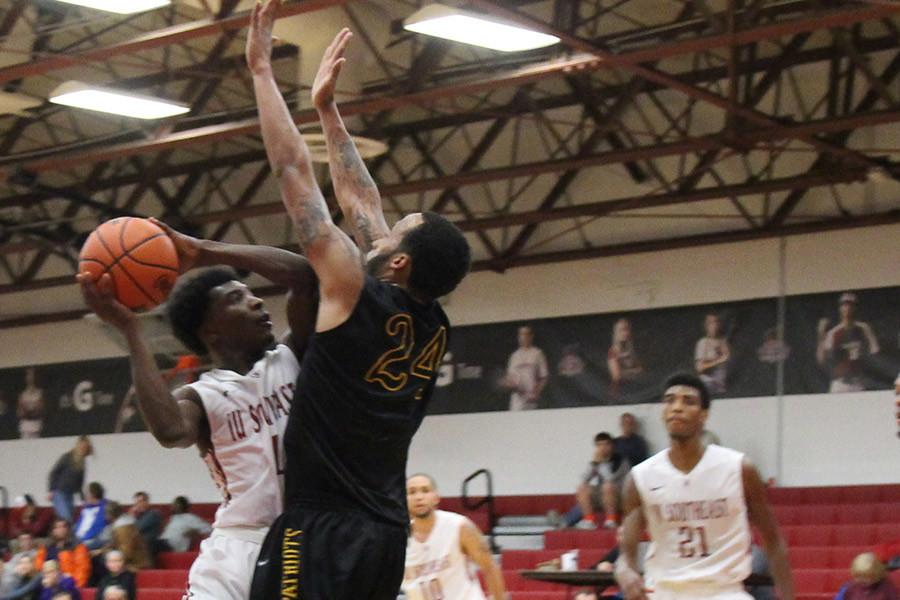 Demetrius Stanton, sophomore guard, goes up for a shot against a St. Catharine defender. Stanton had a game-high 25 points in the loss.