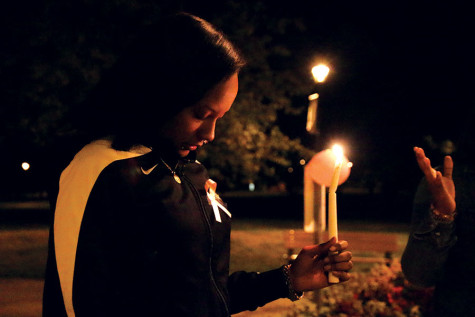 Francesca Komora, sociology junior, holding a candle while they say a prayer at the beginning.