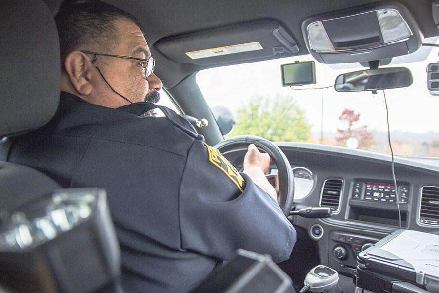 Officer Ruben checks for traffic before merging into  the street to check for parking passes on campus.