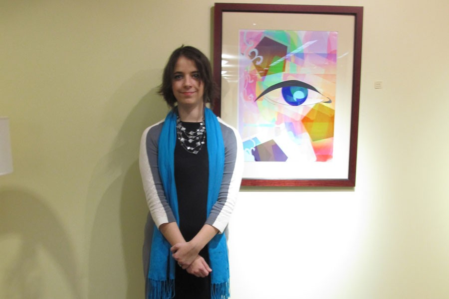 Reba Potter, fine arts senior, stands next to a piece from her B.A. senior art exhibition on Thursday, Jan. 14.