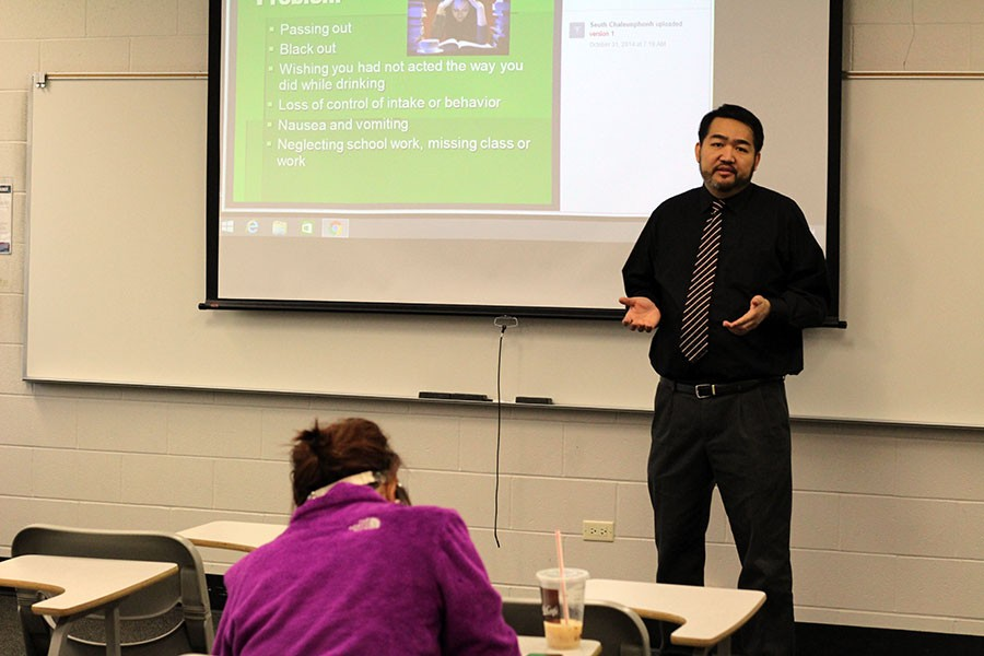 Seuth Chaleunphonh presents a lecture on alcohol education to a student on Friday, Feb. 12.