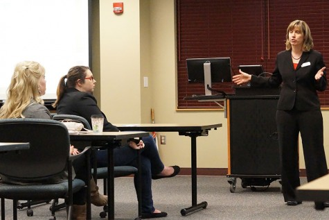 Melissa Fry, assistant professor of sociology and director of the Applied Research and Education Center at IU Southeast, tells a story about one of her clients who lost everything as Annell Lough, outreach advisor for the Center for Women and Families, and another attendee listen.