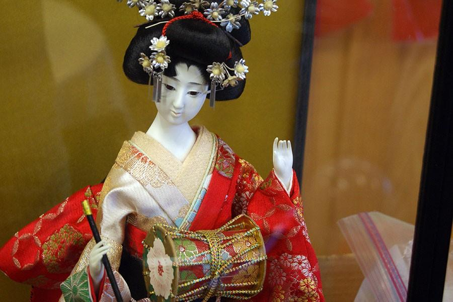 A glass cased statue of a Geshi, the name of a performer of traditional Japanese theater, on display.
