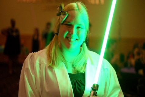 Cendra Stacey, criminal justice and psychology senior, president of the Asian Pop Culture Club and cosponsor of the Spring Ball, dresses as Yoda and holds a green lightsaber in one hand.
