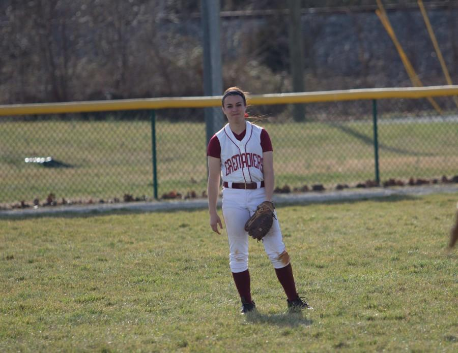 Junior outfielder Brooke Barnett warming up between innings.