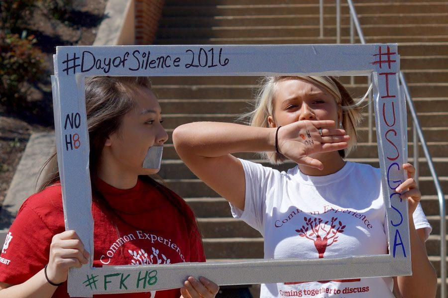 Thalia Tolentino, business freshman, and Taylour Corbett take pictures in their Day of Silence frame, covering their mouths to symbolize silence.