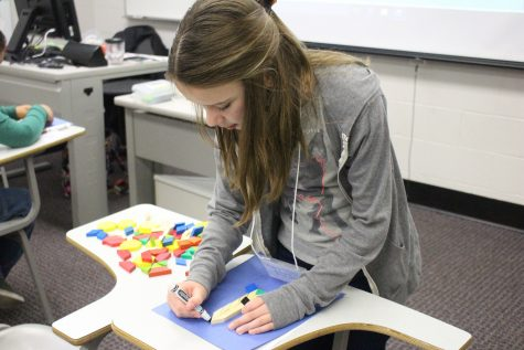 A student working on geography by tracing blocks.