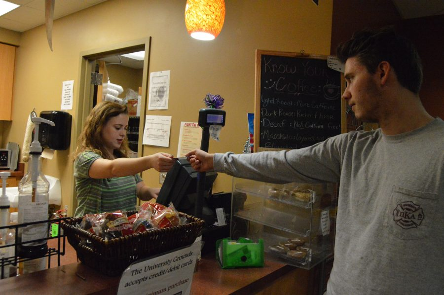 """Political science student Reed Van Dueson uses his UCard to buy coffee on campus from the coffee shop worker and psychology and fine arts senior Claire Faith.  """"I think [the new card] is good,"""" Van Dueson said. """"I've seen flyers around advertising for it and I think it'll be helpful because I go to IU Bloomington a lot.""""  Faith, notified of the change through email, said students use their UCard in about 85 percent of purchases."""