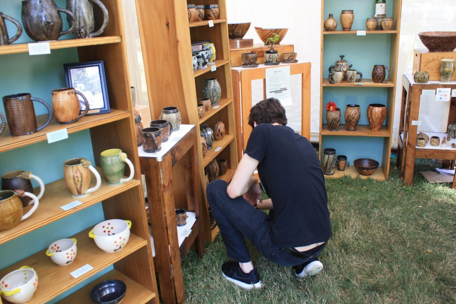 """Ethan Johnson, IUS Senior and son of Art In Speed Park Director, visiting artist, Jennifer Meeker's booth, a potter from Indianapolis, IN.  """"I always try to pick up a piece from one of the booths every year, it's something fun and easy to get a cool collection of things going."""" Johnson said this year, it was mugs he was in search of, Jennifer Meeker's specialty."""