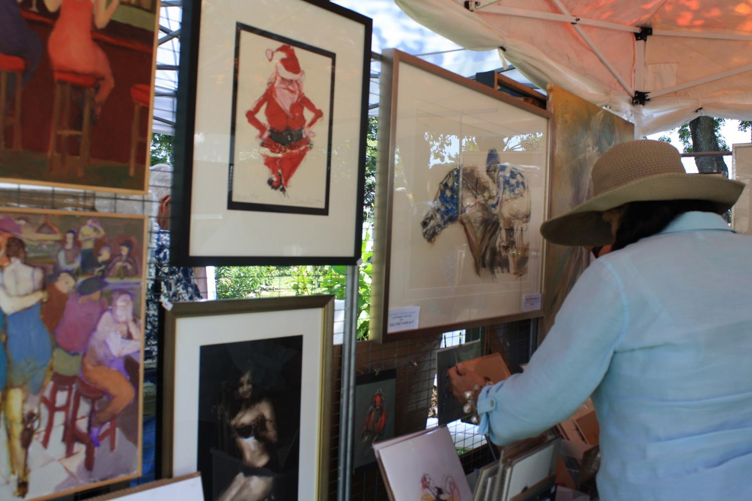 Park goers, observing prints and paintings by Jeaneen Barnhart, a local Louisville and longtime Art In Speed Park featured artist. Barnhart's most popular piece, Secretariat, a depiction of the 1973 Triple Crown champion (far right) was featured at Barnhart's booth as well.