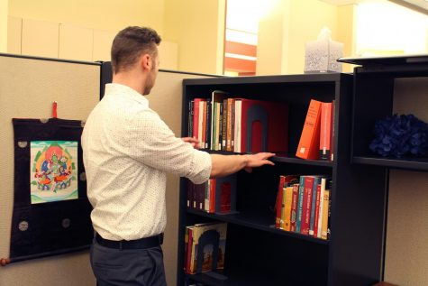 Christopher Proctor, Coordinator of Access Services and Campus Accreditation Project Manager at the IU Southeast Library, shows some of his nearly 2,000 books in his personal collection.