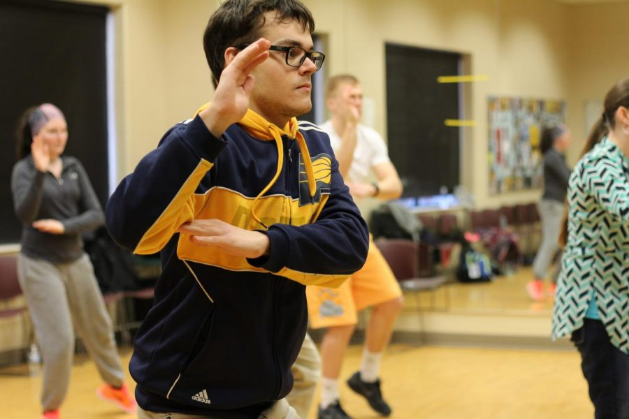 """Max Thieman, IU Southeast student currently taking Tai-chi Basics, warms up with a move called """"Hands in the Clouds."""""""