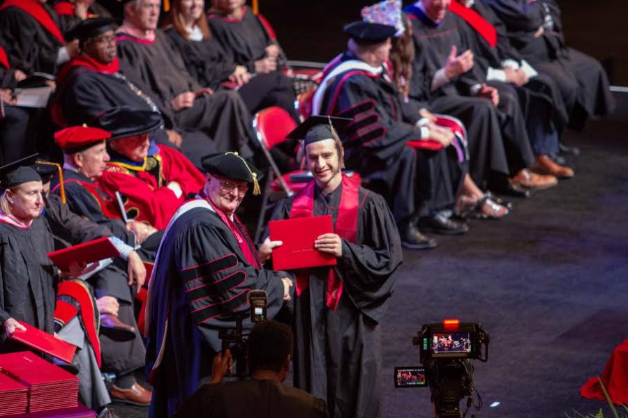 Jackson Tinkle held his diploma with a smile as he received it from Chancellor Wallace. The Chancellor presented each eager student with their diplomas as they crossed the stage. He shook their hands to send them off.