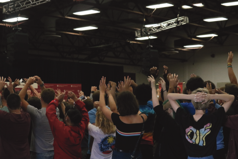 Students raise arms in the air as they do the wave at new student induction day.
