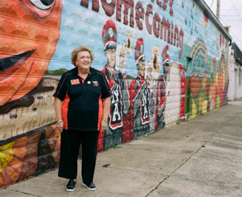 Polly Niemeier stands in front of a mural painted on the Harvest Homecoming office building.