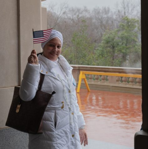 Cuban refugee Arianna Martinez waves an american flag to show support. Small american and Kentucky state flags were passed around to anyone that wanted tone.