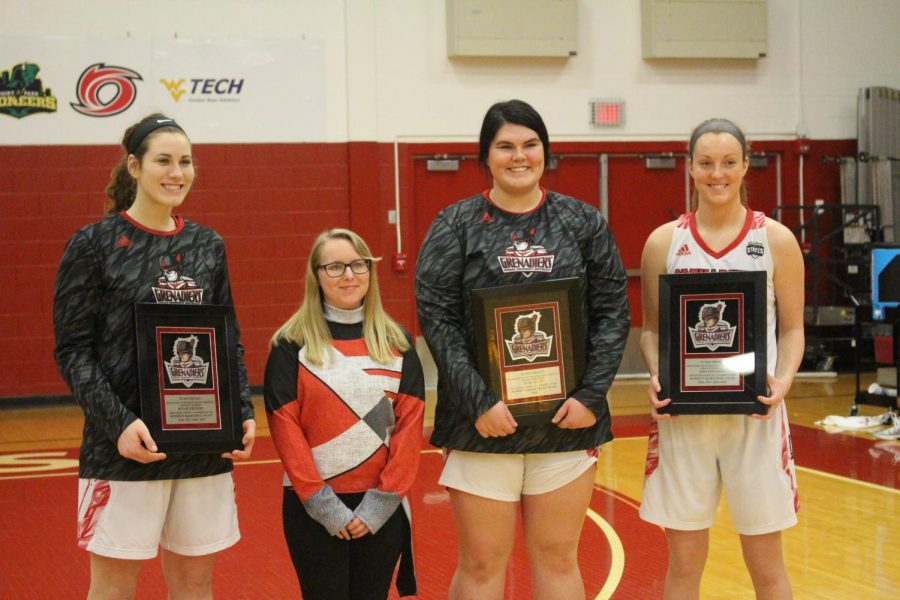 (From left to right) Baylee Kreuger, IUS Pep Band senior Kristina Peter, Kelsi Scott, and Josie Hockman pose for pictures prior to the Grenadiers' game versus Brescia. Photo by Brandon Miniard