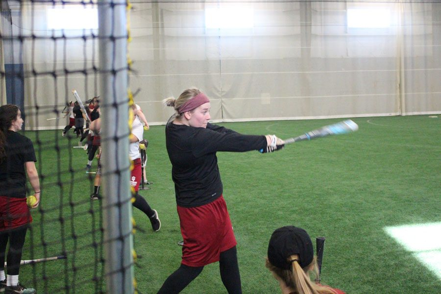 Sydney Seger hits off a tee during batting practice at the Silver Street Park indoor facility in New Albany.