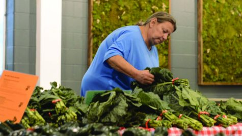 Anita Rodriguez picks out a bundle of produce to add to her bag. Rodriguez is a New Albany resident and regular patron of Fresh Stop Market.