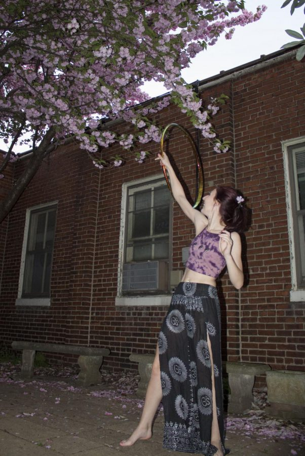 Out in the courtyard at Unity of Louisville, Kelcy Lewis flow with her hula hoop under a blooming tree.