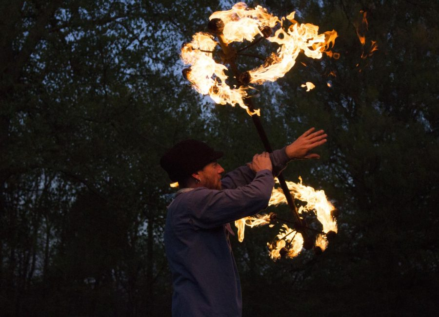 Daniel Crawford (Waldo) rolls a lit dragon staff across his arm during a night flow jam session at Cherokee Park.