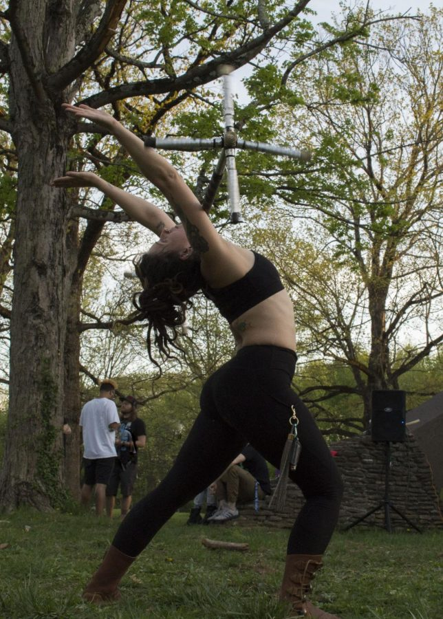 Weslyn Clark (Wezzy Wolven) stands in a yoga pose, warrior one, as her dragon staff rolls down her chest.