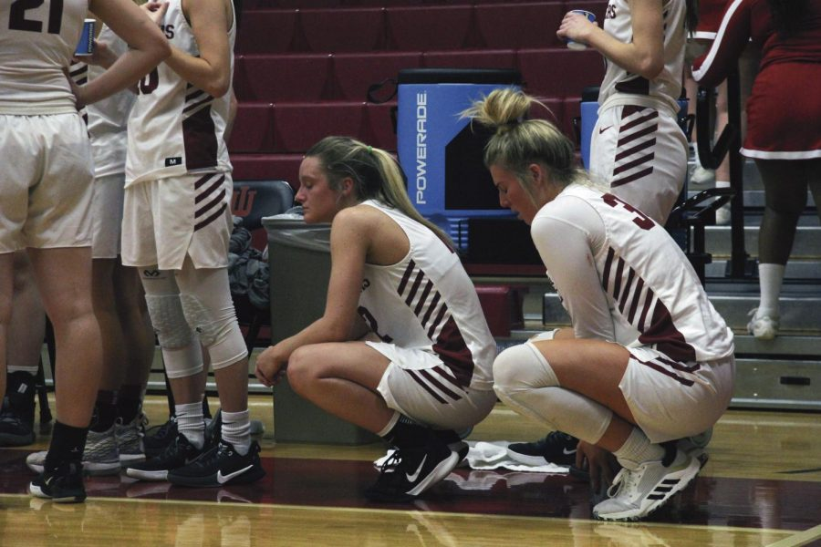 Members of the IUS Women's basketball team crouch on the sidelines shortly before suffering a 95-82 loss in their final game of the season.
