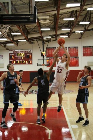 Freshman Forward Trey Hourigan elevates to score after drawing a foul against Oakland City