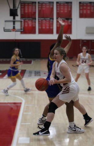 Freshman guard Leah Miller gets a body check from Midway