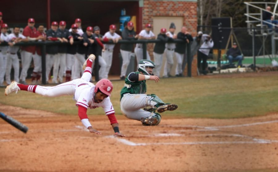 Santrel Farmer slides past home plate after colliding with Huntington catcher Eli Knust during a doubleheader on Feb. 27.