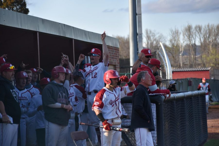Junior utilityman Tyler Mills, (#12), attempts to keep spirits high in the dugout during the tense opener of a crucial three-game series against Asbury on Friday, March 26. The Grenadiers battled through 10 innings before winning 7-6 in the bottom the 11th.