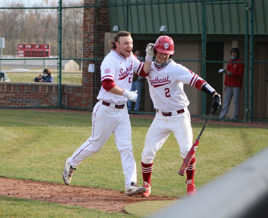 Drew Hensley (left) and Clay Woeste celebrate after the former hit an RBI bloop single, giving the Grenadiers a 1-0 lead during the day game of a doubleheader against IU Kokomo. The breakthrough hit eventually led to a 10-0 Grenadier victory.