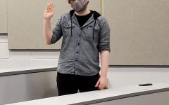 Senior political science major Evan Hunter raises his right hand as he is sworn in as the new SGA vice president during a meeting on March 5.
