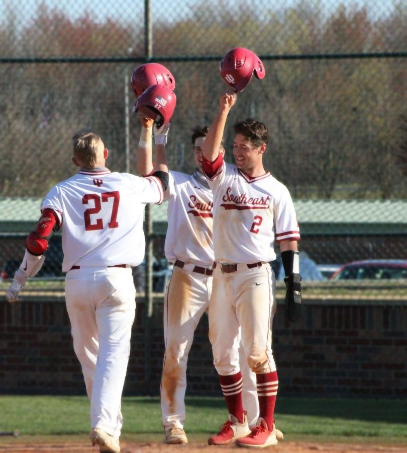 Junior catcher Brody Tanksley (#27) taps helmets with teammates Matt Monahan (center) and Clay Woeste after smashing a three-run home run against Oakland City in the nightcap of a doubleheader on April 3. The homer was Tanksley's second big fly on the day after hitting a two-run shot in the day game of the twin billing.