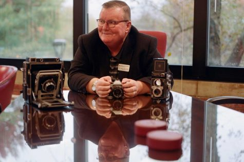 Former chancellor Ray Wallace sits in his office with some of his cameras.