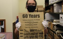 Student Ben-Shalom holds up the 60th anniversary edition of IUS's The Horizon