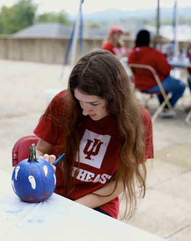 Rayna Kelley takes time between classes at IUS to paint a ghost pumpkin.